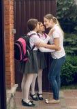 Imagen entonada de dos muchachas que besan a la madre antes de irse a la escuela Foto de archivo