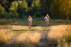 Imagen entonada de dos muchachas que montan las bicicletas en prado en la puesta del sol Imagenes de archivo