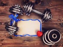 Imagen entonada de las pesas de gimnasia del metal, de la cinta azul del atlas, del corazón rojo y de una hoja del papel del arte Fotografía de archivo