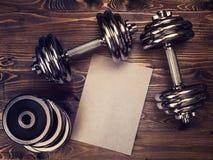 Imagen entonada de las pesas de gimnasia del metal y una hoja del papel del arte Fotografía de archivo libre de regalías