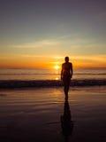 Imagen entonada de una silueta de una mujer adulta que camina en la playa en la puesta del sol Imagen de archivo