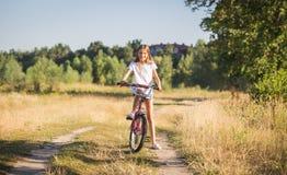 Imagen entonada del adolescente sonriente hermoso que presenta en la bicicleta en campo Imagen de archivo