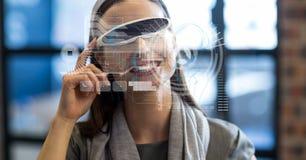 Imagen generada Digital de diversos iconos con la empresaria que usa los vidrios de VR en oficina Fotografía de archivo libre de regalías