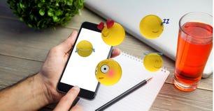 Imagen generada Digital de los emojis que vuelan sobre la mano usando el teléfono elegante por la bebida en la tabla Fotografía de archivo