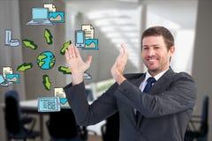 Imagen generada Digital del hombre de negocios que gesticula con los diversos iconos mientras que trabaja en oficina Imagen de archivo