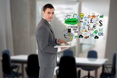 Imagen generada Digital del hombre de negocios usando el ordenador portátil con los diversos iconos en oficina Imágenes de archivo libres de regalías