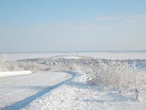 Imagen hermosa del invierno landscape El camino se cubre con nieve y el pueblo en la distancia con las casas nevadas fotografía de archivo