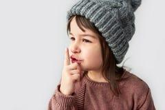 Imagen horizontal del primer de la niña hermosa linda en el sombrero gris caliente del invierno, el suéter que lleva y mostrar ge fotos de archivo libres de regalías