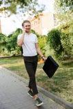 Imagen integral del hombre de negocios rizado contento con la cartera imagen de archivo