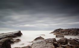 Mar y rocas brumosos Imágenes de archivo libres de regalías