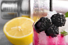 Imagen macra de una bebida de restauración con el limón y las zarzamoras Un cóctel en un fondo borroso Bayas sanas y imagen de archivo libre de regalías