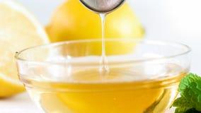 Imagen macra del goteo natural de la miel de la abeja de la cuchara del metal en el tarro de cristal Foto de archivo libre de regalías