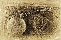 Imagen macra del reloj de bolsillo viejo del vintage en el libro antiguo Visión superior imagen filtrada retra, foto del viejo es Fotos de archivo libres de regalías
