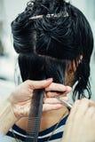 Imagen macra del tiro del primer del pelo de la mujer del cliente del corte del peluquero del peluquero en salón con las tijeras  Imagen de archivo libre de regalías