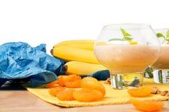 Imagen macra del vidrio del postre aislada en un fondo blanco Smoothie al lado de plátanos y de albaricoques secados Imagenes de archivo