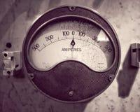 Imagen monocromática de un amperímetro industrial del metal redondo viejo con un dial y una escala análogos imagen de archivo libre de regalías