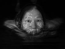 Imagen monocromática de una mujer que flota en agua Fotografía de archivo libre de regalías