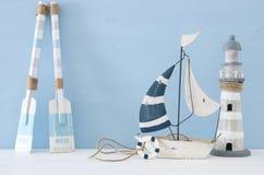 imagen náutica del concepto con los remos, el barco y el faro decorativos sobre fondo azul claro fotos de archivo libres de regalías