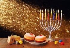 Imagen oscura del día de fiesta judío Jánuca con el menorah, los buñuelos y los dreidels de madera (top de giro) imagen filtrada  Foto de archivo