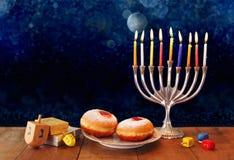 Imagen oscura del día de fiesta judío Jánuca con el menorah, los buñuelos y los dreidels de madera (top de giro) imagen filtrada  Foto de archivo libre de regalías
