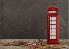 Imagen otoñal con las hojas de arce secas y la cabina de teléfono británica roja Imágenes de archivo libres de regalías