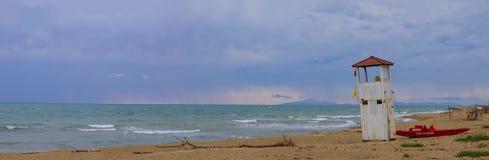 Imagen panorámica de un paisaje marino con la playa solitaria de la arena y un lif imagen de archivo