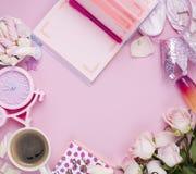imagen plana de la endecha Accesorios del ` s de las mujeres, café de la mañana y flores de las rosas blancas en un fondo rosado  Imagen de archivo