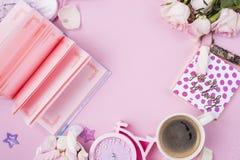 imagen plana de la endecha Accesorios del ` s de las mujeres, café de la mañana y flores de las rosas blancas en un fondo rosado  Foto de archivo