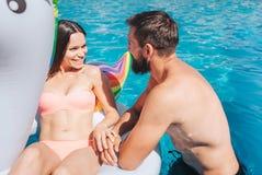 Imagen positiva de la natación magnífica de los pares en piscina La muchacha está mintiendo en el colchón de aire Miran uno a y s foto de archivo