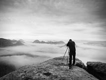 Imagen que enmarca del fotógrafo con el ojo en el visor El entusiasta de la foto disfruta del trabajo, naturaleza de la caída Foto de archivo