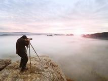 Imagen que enmarca del fotógrafo con el ojo en el visor El entusiasta de la foto disfruta del trabajo, naturaleza de la caída Fotografía de archivo