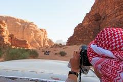 Imagen que toma turística de una conducción de automóviles a través del desierto de Wadi Rum, Jordania Fotos de archivo libres de regalías