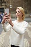 Imagen que toma turística femenina magnífica con su smartphone mientras que se coloca al aire libre en calle de la ciudad Fotografía de archivo