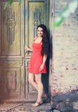 Imagen retra de la muchacha linda cerca de la puerta vieja Foto de archivo