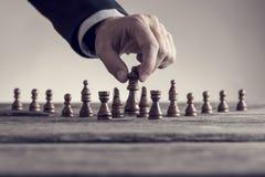 Imagen retra de un hombre que juega al ajedrez que mueve el pedazo de la reina Fotografía de archivo libre de regalías