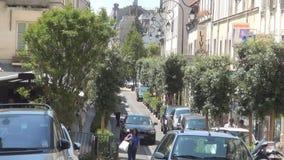 Imagen Rue Ybry con tráfico de coche y gente de la calle de París que camina en la acera