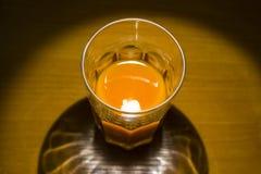Imagen simple de un vidrio con el zumo de naranja en el escritorio imagenes de archivo