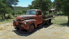 Imagen soleada del verano de una camioneta pickup anaranjada roja del vintage en una granja stock de ilustración
