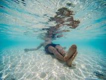 Imagen subacuática de un hombre joven que se acuesta en la orilla de la playa Agua azul clara imagenes de archivo