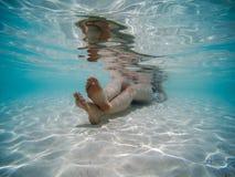 Imagen subacuática de una mujer joven que se acuesta en la orilla de la playa Agua azul clara imagenes de archivo
