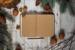 Imagen superior del libro abierto con las páginas en blanco del vintage y las decoraciones de la Navidad en una tabla de madera N Imagen de archivo libre de regalías