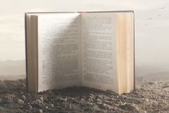 Imagen surrealista de un libro gigante abierto en el medio de la naturaleza fotos de archivo