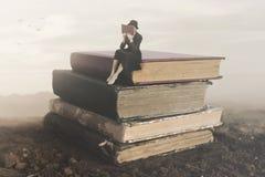 Imagen surrealista de una lectura de la mujer que se sienta encima de un libro imagen de archivo libre de regalías