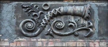 Imagen tridimensional grabada en relieve en la pared de una casa vieja sobre el ladrillo: tubo curvado largo bajo la forma de cás Imágenes de archivo libres de regalías