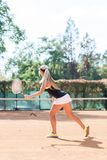 Imagen vertical del jugador de tenis de sexo femenino rubio caucásico en la acción, al aire libre Visión desde la parte posterior Fotos de archivo libres de regalías