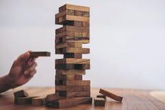 Imagens da mão dos empresários que colocam e que puxam o bloco de madeira Imagem de Stock Royalty Free
