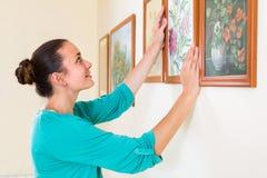 Imagens de suspensão da menina nos quadros na parede na casa Imagem de Stock Royalty Free