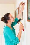 Imagens de suspensão da menina nos quadros na parede na casa Fotografia de Stock