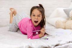 Imagens de tiragem da menina bonito ao encontrar-se na cama fotografia de stock royalty free