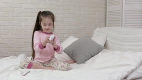 Imagens de tiragem da menina bonito ao encontrar-se na cama